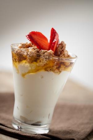 comiendo cereal: Desayuno con yogurt natural, muesli y miel Foto de archivo