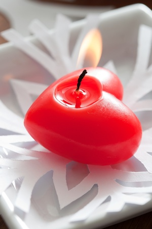 burning love: Red heart candle on white paper snowflake