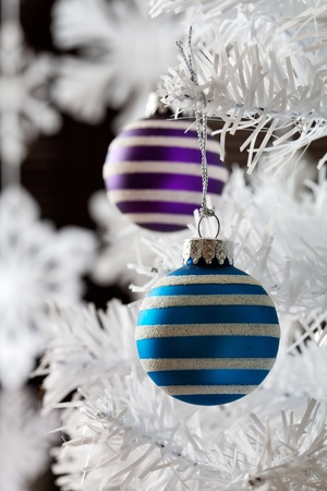 Colourful christmas baubles hanging from white christmas tree photo