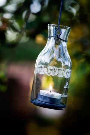 Beautiful glass lantern hanging from apple tree