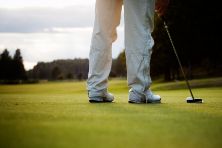 golf swing: Male golfer putting a golf ball in to hole