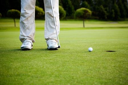 pelota de golf: Golfista masculino que pone una pelota de golf en el agujero para