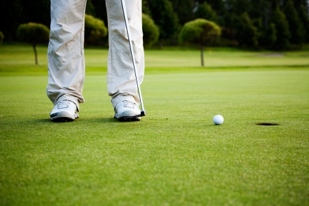 golf club: Male golfer putting a golf ball in to hole