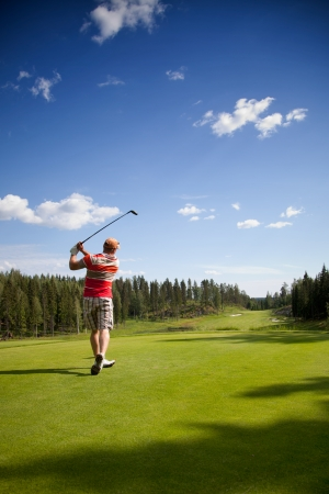 Male golfer shooting a golf ball photo