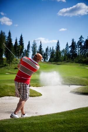 swings: Golfista masculino rodar una pelota de golf de la arena Foto de archivo