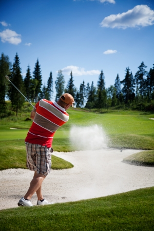 Male golfer shooting a golf ball from sand photo