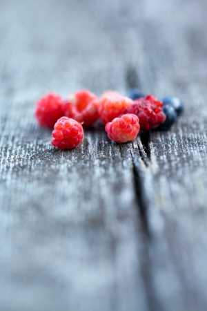 Fresh blueberries and raspberries on wooden background photo