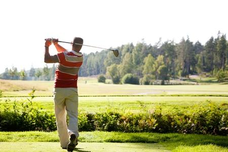 緑の芝生からのゴルフボールを撮影男性ゴルファー