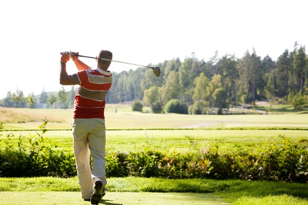 Male golfer shooting a golf ball from green grass Stock Photo - 14843710