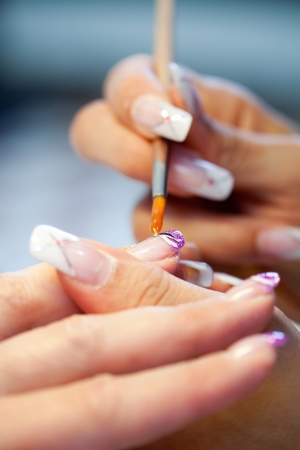 Woman getting artificial nails done, selective focus
