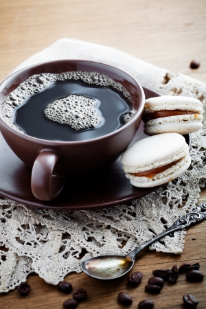 Cup of hot coffee with french macaroon photo
