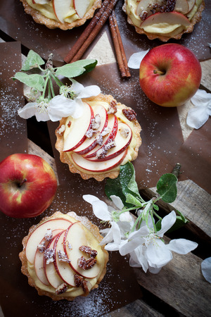 Tartlets with apple slices, cream and pecan filling photo
