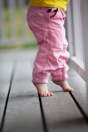 bare feet toes: Little girl reaching up Stock Photo