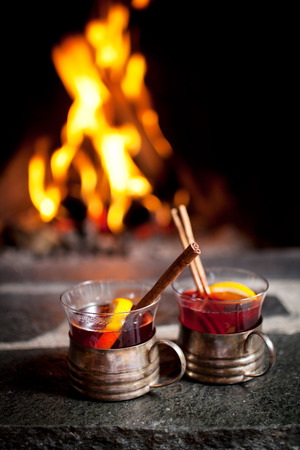 vin chaud: Mulled wine with cinnamon stick by the fireplace Banque d'images