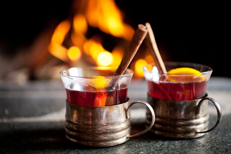 Mulled wine with cinnamon stick by the fireplace Stock Photo