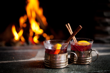 Mulled wine with cinnamon stick by the fireplace Imagens