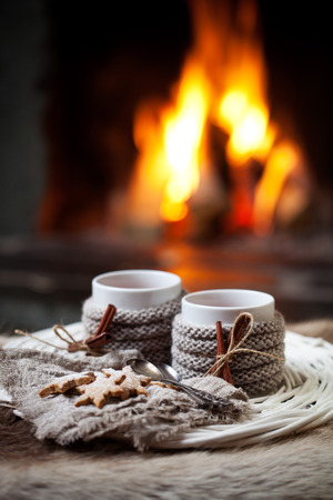 winter season: Mulled wine with cinnamon stick by the fireplace Stock Photo