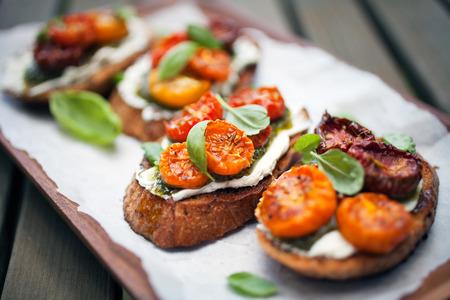 comida italiana: Bruschetta con medio seca tomates y albahaca