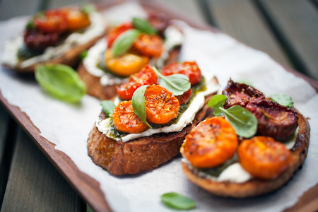 snack food: Bruschetta with half dried tomatoes and basil Stock Photo