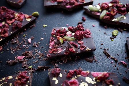 Handmade chocolate with berries, jpistachios and edible gold
