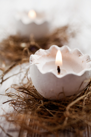 easter candle is burning: Easter egg shell candles on top of nest