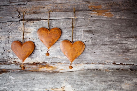 oxidado: corazones rústicas colgadas contra la madera desgastada