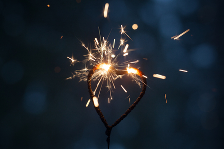 Heart shape sparkler burning in the dark Stock Photo