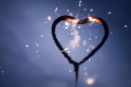 心臓形状線香花火の燃焼と暗闇の中で輝く 写真素材
