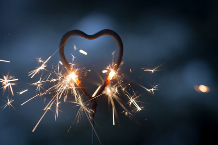 Heart shape sparkler burning and glowing in the dark Stock Photo