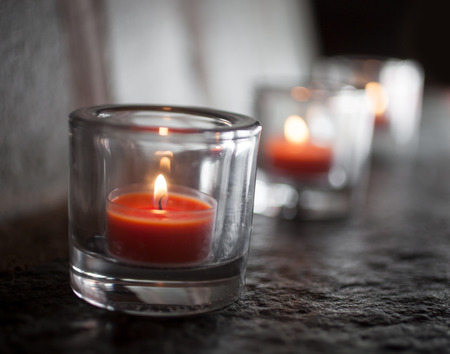 Three tealights burning and glowing in the dark Stock Photo - 74806086