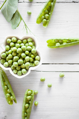 Fresh green peas on white table Banco de Imagens - 104886651