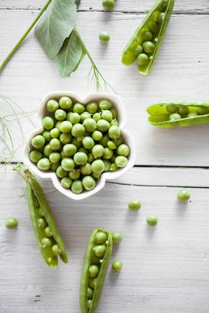 Fresh green peas on white table Banco de Imagens
