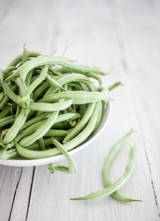 Group of green beans on white wooden table background