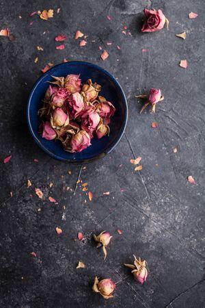 Dried pink rose buds on dark