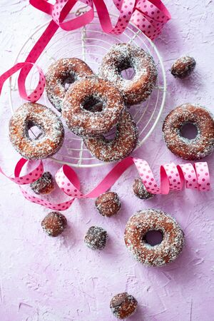 Sugar donuts and pink ribbon on pink background