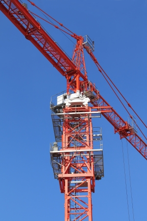 Red building crane on blue sky