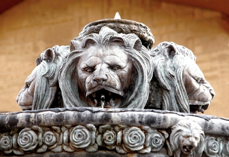 Fountain in a form of big and old lion statue and flowers