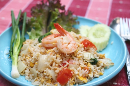 Shrimp fried rice with eggs, onion and tomato on blue plate Stock Photo