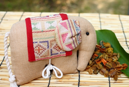 Herb package in a form of elephant with thai cloth, put on table cloth made from wooden Stock Photo