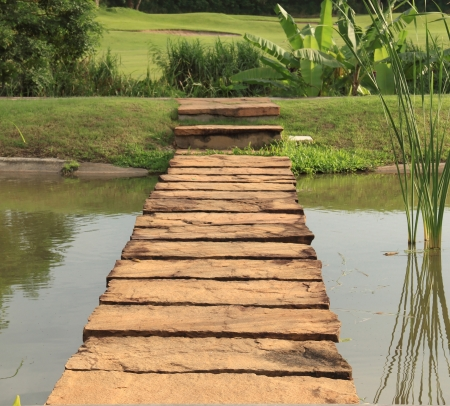 calmness: Stone path across pond lead to green garden Stock Photo