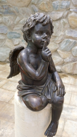 Cupid statue sitting made from black marble stone Stock Photo