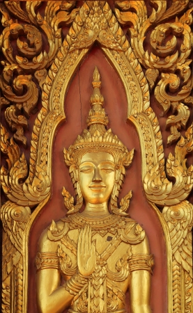 Close up ancient golden carving wooden door of temple in Ayutthaya, Thailand