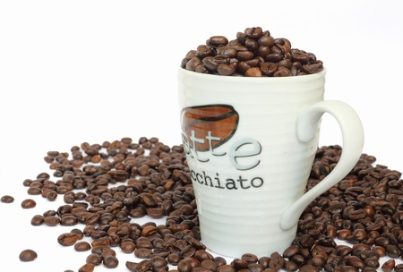 Cup full of coffee beans on white background