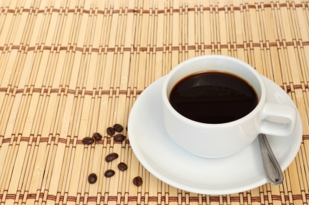 Cup of coffee with some coffee beans next to the cup, put on the table cloth made from wooden