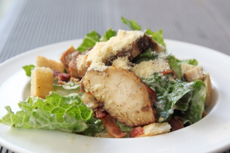 Closeup chicken ceasar salad in a white plate photo
