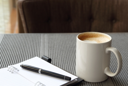 Hot coffee latte in white cup with journal book and pen