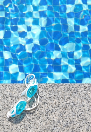 Blue swimming goggles on swimming pool background photo