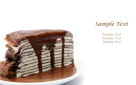 Close up crape cake with chocolate sauce isolated on white with space for text photo