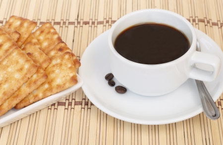 Cup of coffee and cracker on a white plate