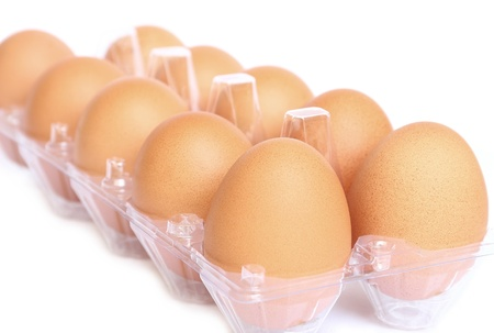 Eggs in the plastic package on white background
